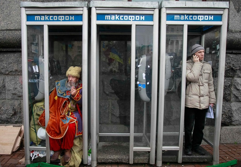 A man dressed in traditional Ukrainian Cossack clothes smokes in a phonebooth during a rally to support EU integration in Kiev